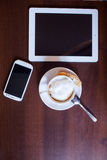 Cup of Cappuccino and mobile phone and tablet pc on wooden table Royalty Free Stock Photography
