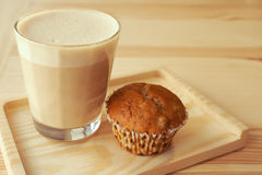 Cup of cappuccino and muffin; selective focus. Glass cup of cappuccino with muffin on a wooden background Stock Image