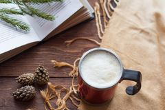 Cup of cappuccino and opened book on wooden background,holiday winter holidays.  stock photos