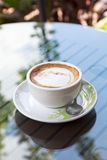 Cup of cappuccino over wooden table Royalty Free Stock Images