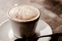 Cup of cappuccino over wooden table Royalty Free Stock Photos