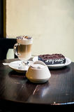 Cup of cappuccino, Piece cake. Cup of cappuccino, a piece of chocolate cake on a plate on a table Royalty Free Stock Images