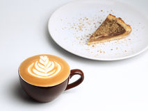 Cup of cappuccino and a piece of cake. Latte art Stock Photo