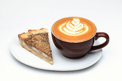 Cup of cappuccino and a piece of cake. Latte art Royalty Free Stock Image