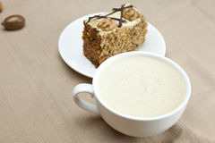 Cup of cappuccino, a piece of cake with nuts Stock Photography