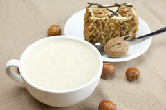 A cup of cappuccino, a piece of cake with nuts Stock Photography