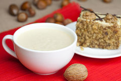 Cup of cappuccino, a piece of cake with nuts Royalty Free Stock Images