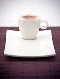 Cup of cappuccino on plate. Cup of frothy cappuccino on a white square plate Stock Photos