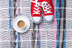 Cup of cappuccino and red gumshoes Royalty Free Stock Photos