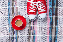 Cup of cappuccino and red gumshoes Stock Photo