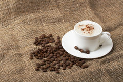 Cup of cappuccino at the sacking. With whole grains of coffee Royalty Free Stock Photo