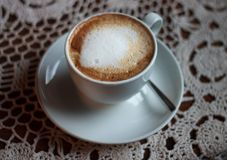 Cup of cappuccino served on table with lace tablecloth Royalty Free Stock Photo