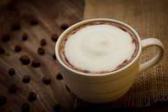 Cup of cappuccino served on wooden table with coffee beans in th Royalty Free Stock Photography