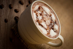 Cup of cappuccino served on wooden table with coffee beans in th Stock Image