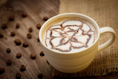 Cup of cappuccino served on wooden table with coffee beans in th Stock Images