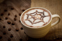 Cup of cappuccino served on wooden table with coffee beans in th Stock Photos