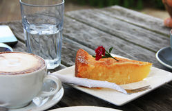 Cup of cappuccino and a slice of cake Royalty Free Stock Image