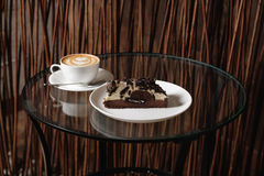 A cup of cappuccino and slice of chocolate cheesecake on a glass table. A cup of cappuccino and slice of tasty chocolate cheesecake on a glass table on wooden Stock Photography