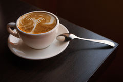Cup of cappuccino on sourcer with spoon standing on the corner of table stock image