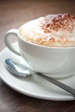 A cup of Cappuccino with a spoon on a brown table Royalty Free Stock Image