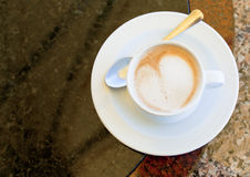 Cup of cappuccino on stone table Stock Photos