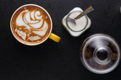 Cup of cappuccino and sugar bowl on black background Royalty Free Stock Photos