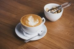The Cup of cappuccino and a sugar bowl with brown sugar on wooden background Stock Photo