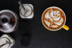 Cup of cappuccino and sugar bowls on black background. Latte art Stock Image