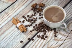 A cup of cappuccino on the table, near the coffee beans, star anise and a bunch of cinnamon. Close-up royalty free stock photography