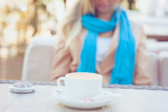Cup of cappuccino on the table in summer cafe. Blonde woman with long hair sitting at the table of summer cafe. A woman dressed in a beige jacket, blue scarf Stock Photo