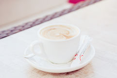 Cup of cappuccino on the table. In summer cafe. on a saucer are a few bags of sugar and a teaspoon Royalty Free Stock Photos