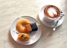 Cup of cappuccino and some little cakes. Cup of cappuccino and three pastries on a plate, standing on a marble table Royalty Free Stock Photography