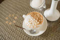 Cup of cappuccino and a vase Royalty Free Stock Photos