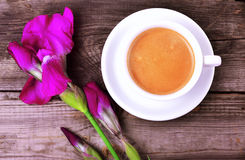 Cup of cappuccino and violet blossoming iris Royalty Free Stock Photos