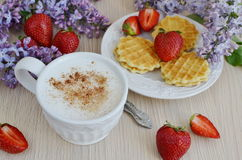 Cup of cappuccino with waffles, strawberries and flowers Stock Image