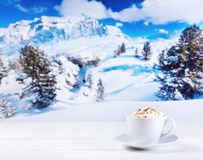 Cup of cappuccino with whipped cream over winter landscape. Cup of cappuccino with whipped cream on wooden table over winter landscape royalty free stock photography