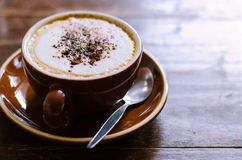 Cup of Cappuccino. A cup of cappuccino on the wood table Royalty Free Stock Photos