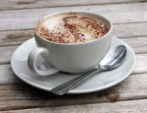 Cup of Cappuccino on wooden slat table Royalty Free Stock Image