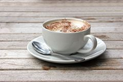 Cup of Cappuccino on wooden slat table. With chocolate stock photography