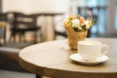 Cup of cappuccino on wooden table. Blurred background cafe behind. royalty free stock photos