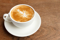 Cup of cappuccino on wooden table. Hot cup of cappuccino on wooden table royalty free stock images