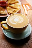 A Cup of cappuccino in a yellow mug on a blue saucer on a wooden table in a cafe. Nearby are Cutlery and a white plate with royalty free stock photos