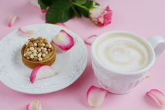 Cup of cappuccino and yummy cake with pink roses Stock Photo
