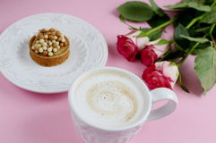 Cup of cappuccino and yummy cake with pink roses Stock Image