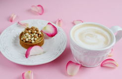 Cup of cappuccino and yummy cake with pink roses. On the table Royalty Free Stock Photography