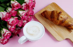Cup of cappuccino and yummy croissant with pink roses Royalty Free Stock Image