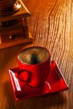 Cup of cappuchino and coffee grinder on wooden board Royalty Free Stock Image