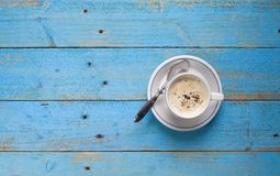 A cup of cappucino. On a blue wooden table, free copy space royalty free stock images
