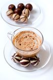Cup of cappucino and candies. Cup of cappucino and chocolate candies stock images
