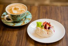 Cup cappucino with heart coffee art a light and airy pavlova`s dessert with merengue and fruit stock photos